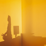 Shadow of a woman meditating in a yellow room