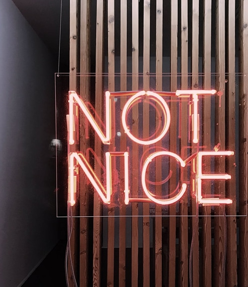 """Red neon sign saying """"not nice"""""""